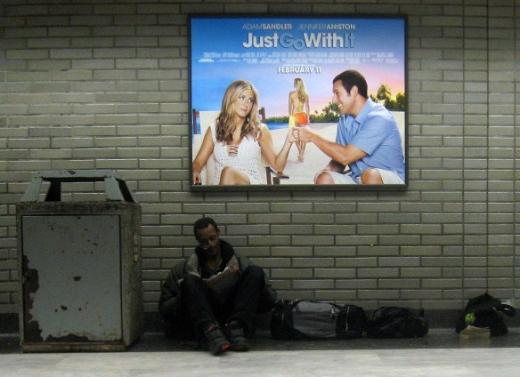 The contrast of homelessness and the bright, shiny life sold by Hollywood as a man reads below a movie poster.