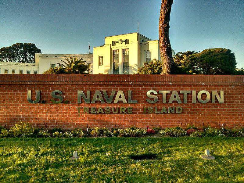 """Brick wall with brass letters announcing """"US Naval Station, Treasure Island"""""""