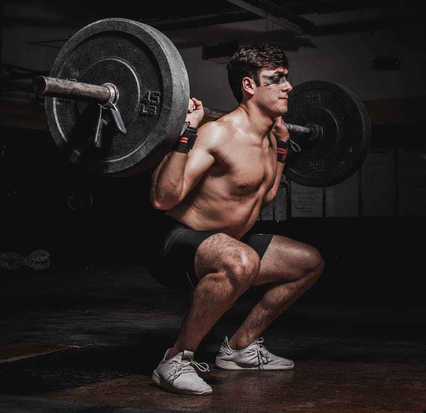 Weight-lifter, with 70 lbs on his bar bell, does a Narrow Stance Squat