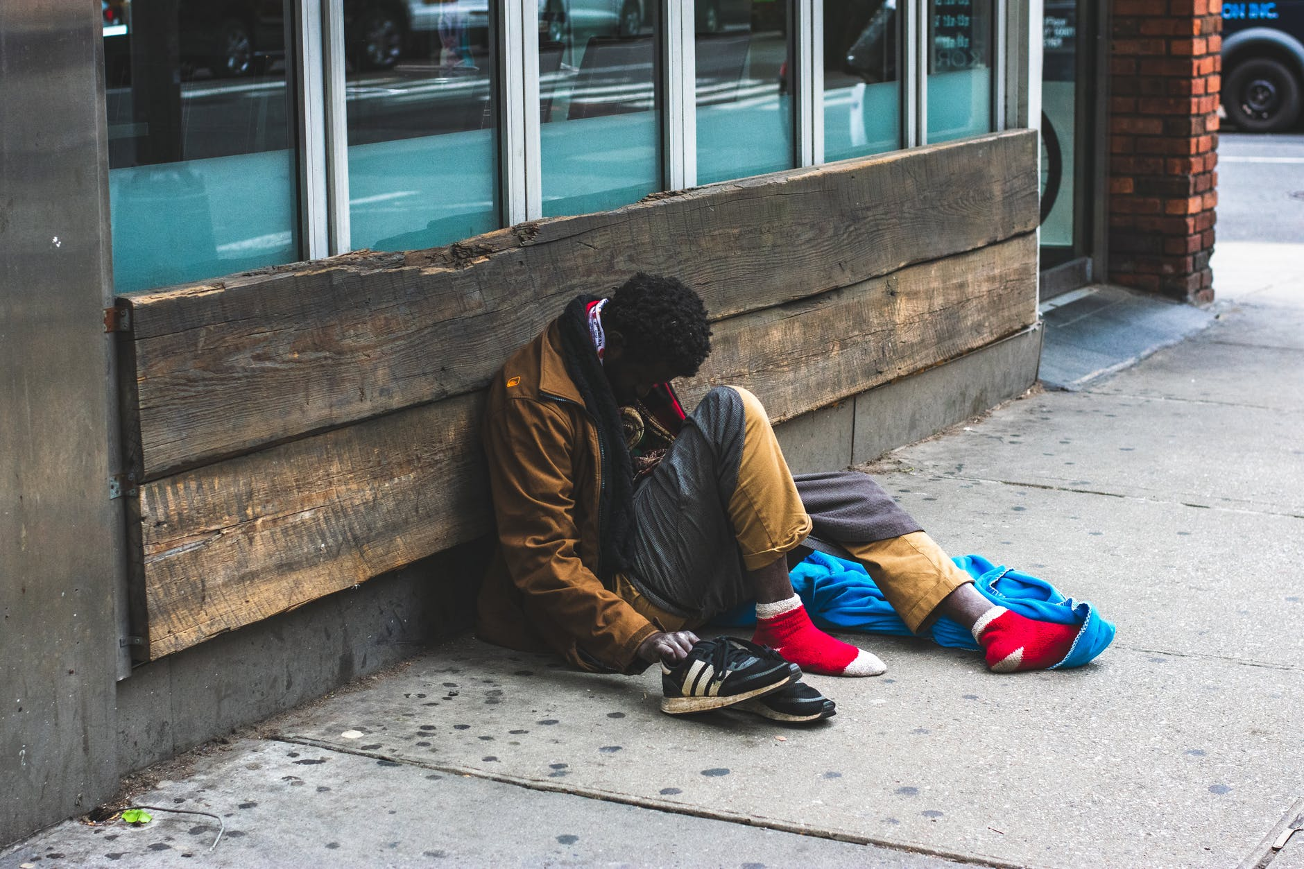 The homeless man sitting directly on the sidewalk, leaning against the storefront, had his shoes off with his legs resting on another jacket