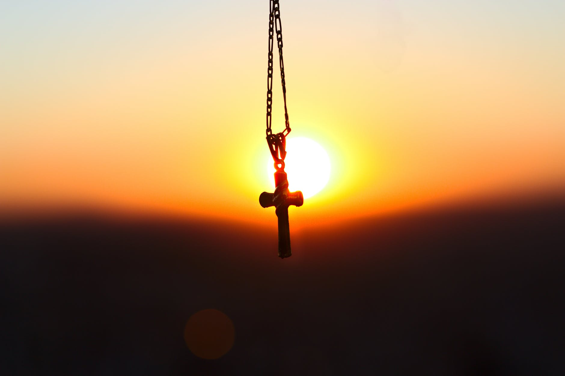 small cross hanging on a chain with setting sun behind it